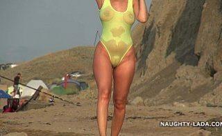 Umbla cu un costum de baie transparent pe plaja